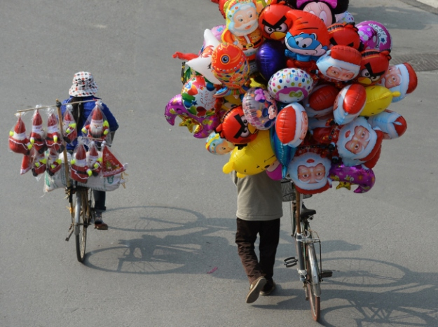 Vendeuse de ballons à bicyclette , Vietnam  Source: nguoivietblog.com
